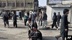 A wounded man is being helped after a suicide blast targeting a Shi'ite Muslim gathering in Kabul December 6, 2011
