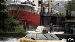 Sebuah taksi terperangkap dalam banjir di bagian barat Manhattan selagi badai Irene menerpa kota New York (Minggu, 28/7).