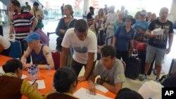 Para penumpang berbicara dengan staf maskapai penerbangan karena penerbangan mereka dari Bandara Internasional Ngurah Rai dibatalkan akibat erupsi Gunung Agung, Selasa, 28 November 2017.