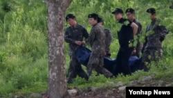 13일 예비군 사격훈련중 총기 사망사고가 발생한 예비군 훈련장에서 군 관계자들이 총기를 난사하고 자살한 예비군의 시신을 들고 이동하고 있다.