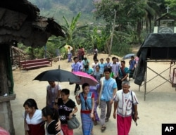 FILE - Karen refugees leave after a church service at Mae La refugee camp in Ta Song Yang district of Tak province, northern Thailand, April 12, 2013.