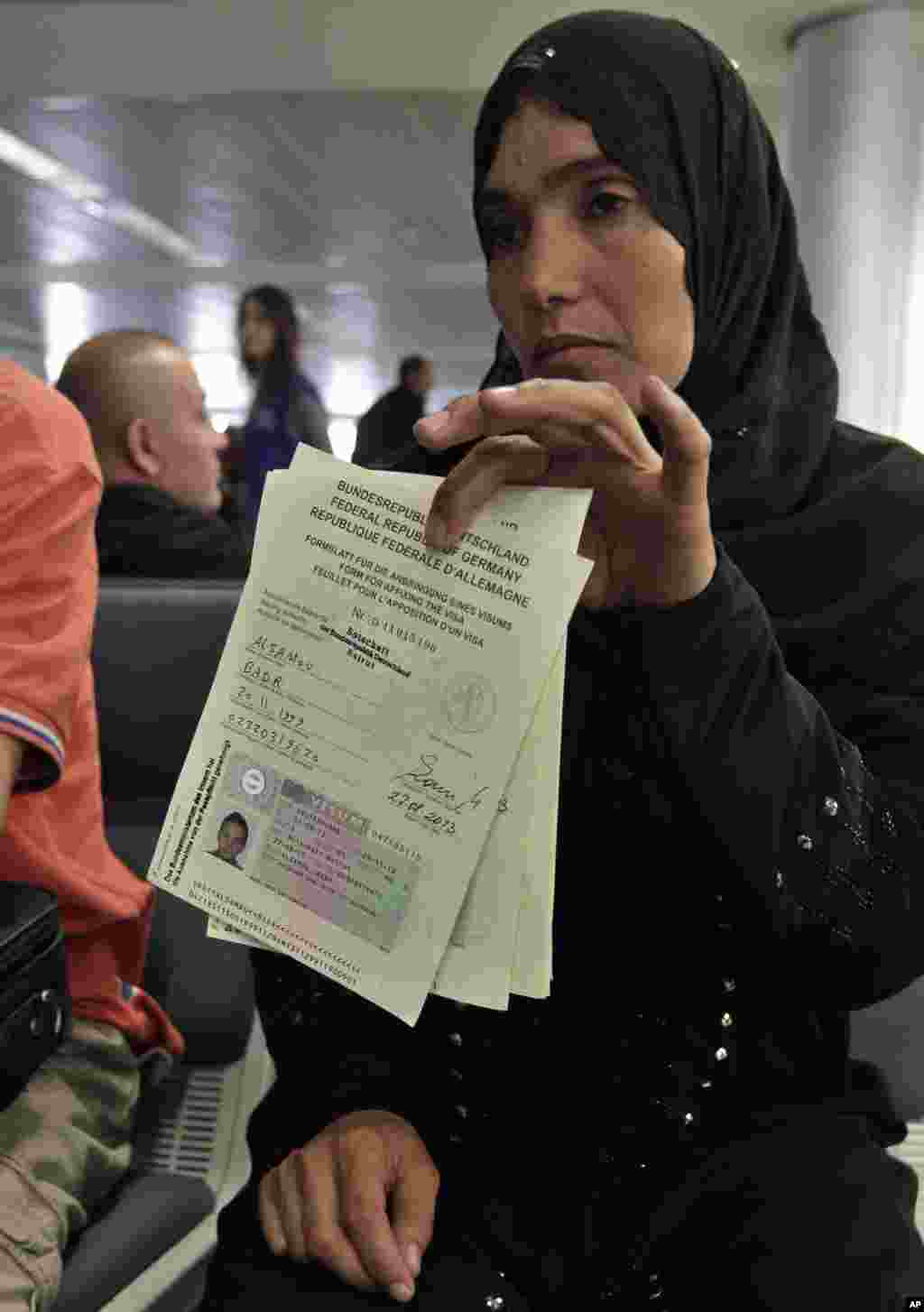 A Syrian refugee shows her immigration papers before boarding a flight to Germany for temporary relocation, at Rafik Hariri International Airport in Beirut, Lebanon, Sept. 11, 2013.