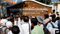 Journalists try to interview a leader of Cambodian activists during a march in front of the Anti-Corruption Unit, in Phnom Penh, Cambodia, Thursday, May 29, 2014. (AP Photo/Heng Sinith)