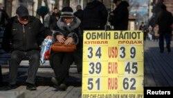 Papan bertuliskan nilai pertukaran mata uang di pusat kota Kyiv, Ukraina (25/2). (Reuters/Valentyn Ogirenko)