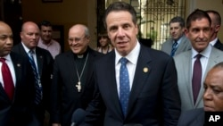 New York Governor Andrew Cuomo, center, talks with the press after a meeting with Cuban Cardinal Jaime Lucas Ortega y Alamino, left, in old Havana, Cuba, April 20, 2015.