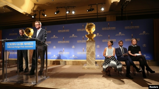 Hollywood Foreign Press Association President Theo Kingma speaks at the podium as (L-R) actors Zoe Saldana, Aziz Ansari and Olivia Wilde sit on stage at the announcement of nominations for the 71st annual Golden Globe Awards in Beverly Hills, California,