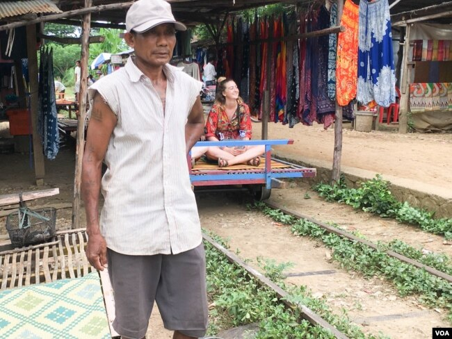 Ngul Nguon, 56, has been the bamboo train driver for almost 20 years. He earns the income from this tourism site. (Sun Narin/VOA Khmer)
