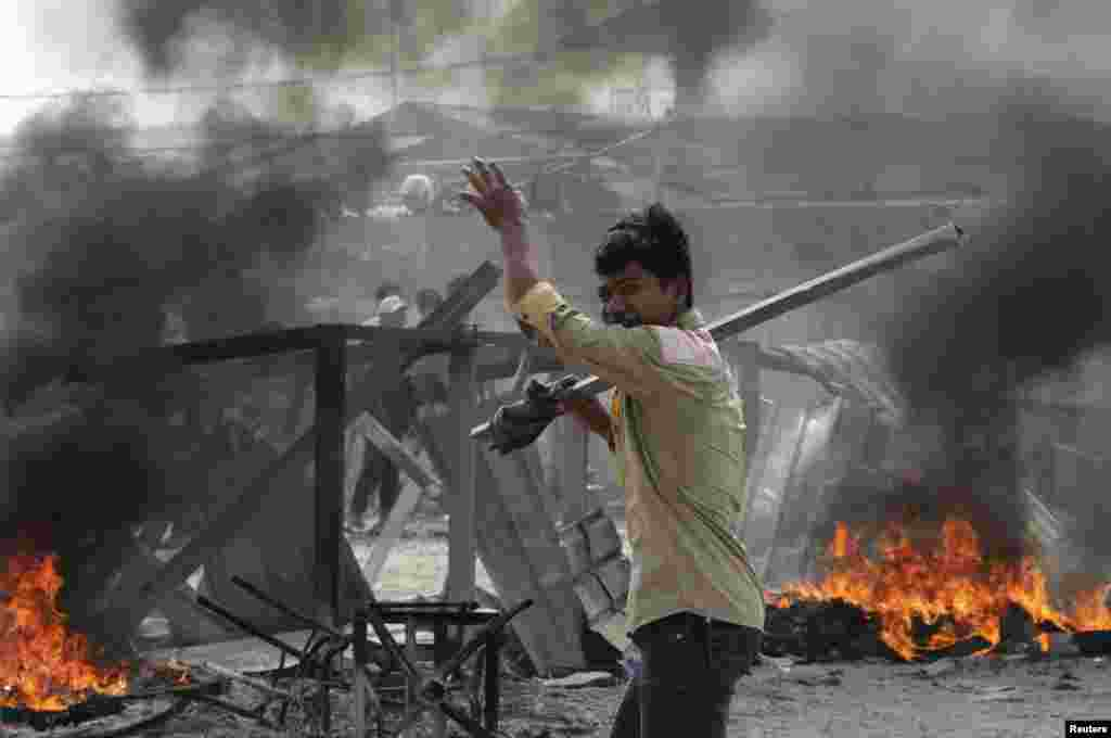 A worker carrying a metal rod reacts after clashes broke out during a protest in Phnom Penh, Jan. 3, 2014.