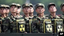 Binh sĩ Bắc Triều Tiên cầm ba lô in biểu tượng hạt nhân nhìn về phía lãnh tụ Kim Jong Un trong một buổi lễ kỷ niệm 60 năm hiệp ước đình chiến chấm dứt Chiến tranh Triều Tiên, ở Bình Nhưỡng, 27/7/2013.