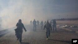 Migrantes corren del gas lacrimógeno lanzado por agentes estadounidenses, entre fotoperiodistas que cubren la frontera entre México y Estados Unidos, después de que un grupo de migrantes lograra pasar a las autoridades mexicanas en el cruce de Chaparral en Tijuana, México.