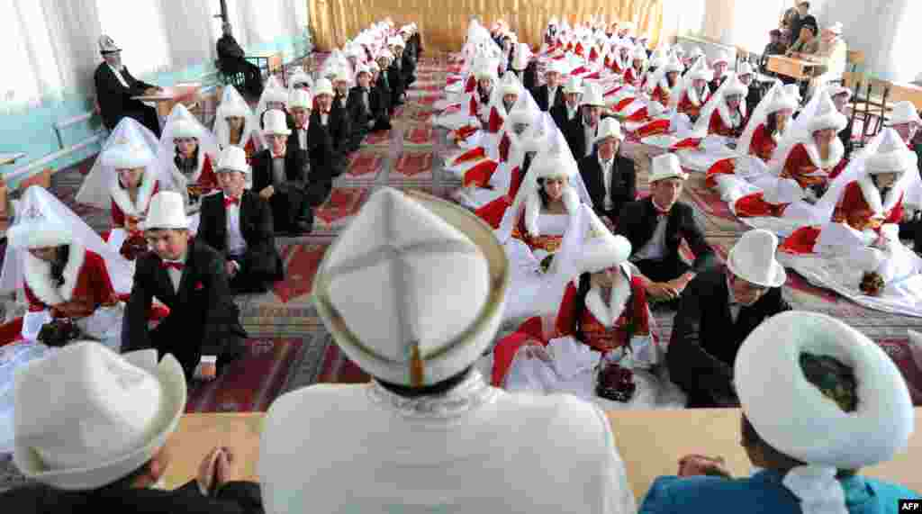Kyrgyz brides and bridegrooms pray in the central mosque during a mass wedding ceremony in the capital Bishkek, Kyrgyzstan.