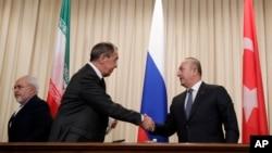 លោក Sergey Lavrov រដ្ឋមន្រ្តីការបរទេសរុស្ស៊ី (រូបកណ្តាល) ចាប់ដៃជាមួយនឹងលោក Mevlut Cavusoglu រដ្ឋមន្រ្តីការបរទេសតួកគី នៅពេលលោក Mohammad Javad Zarif រដ្ឋមន្រ្តីការបរទេសអ៊ីរ៉ង់ (រូបឆ្វេង) ចេញពីសន្និសីទកាសែតរួមគ្នាមួយបន្ទាប់ពីកិច្ចប្រជុំរបស់ពួកគេ នៅក្នុងក្រុងមូស្គូ កាលពីថ្ងៃទី២០ ខែធ្នូ ឆ្នាំ២០១៦។