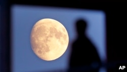 FILE - A student leaves his residence as the moon rises over Frankfurt, Germany, Nov. 1, 2017.