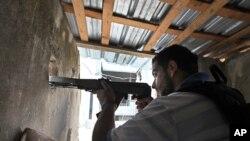 شامی حکومت کے حامی اور مخالفین کے درمیان مسلح جھڑپوں میں ایک شخص نشانہ باندھے بیٹھا ہے