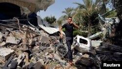 یک فلسطینی در میان ویرانه های یک مرکز توانبخشی که به گفته پلیس فلسطین مورد حمله تانک های اسرائیلی قرار گرفته است. ۲۱ تیر ۹۳