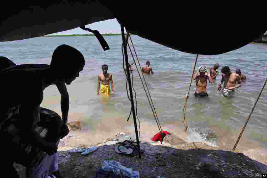 "Bangladeshi men wash themselves in the sea near a temporary shelter in Langsa, Aceh province, Indonesia, May 19, 2015. Indonesia's foreign minister said that her country has ""given more than it should"" to help hundreds of Rohingya and Bangladeshi migrants stranded on boats by human traffickers."