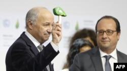 法國外長法比尤斯(左)敲打小槌,宣佈全球氣候協議獲得一致通過。旁為法國總統奧朗德。