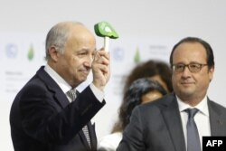 Foreign Affairs Minister and President-designate of COP21 Laurent Fabius, left, waves the official gavel of the conference, as France's President Francois Hollande looks on, after adoption of a historic global warming pact, Dec. 12, 2015.