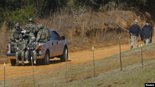 Law enforcement officials including the FBI at the scene of a shooting and hostage taking near Midland City, Alabama February 1, 2013.