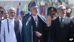 Afghan President Hamid Karzai, center, speaks in front of local and international media representatives as presidential candidates Abdullah Abdullah, right, and Ashraf Ghani Ahmadzai, left, listen during the Independence Day ceremony in Kabul, Afghanistan