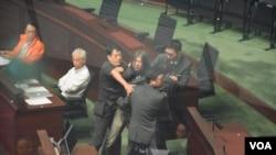 社民連立法會議員梁國雄(長髮者)被多名保安人員合力帶離會議廳。(美國之音 湯惠芸攝)