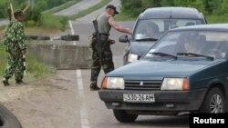 Separatistas prorrusos revisan vehículos en un puesto de control cerca de la ciudad de Lugansk, en el este de Ucrania.