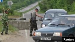 Dân quân thân Nga khám xét xe cộ tại một chốt kiểm soát bên ngoài làng Schastya, miền đông Ukraine.