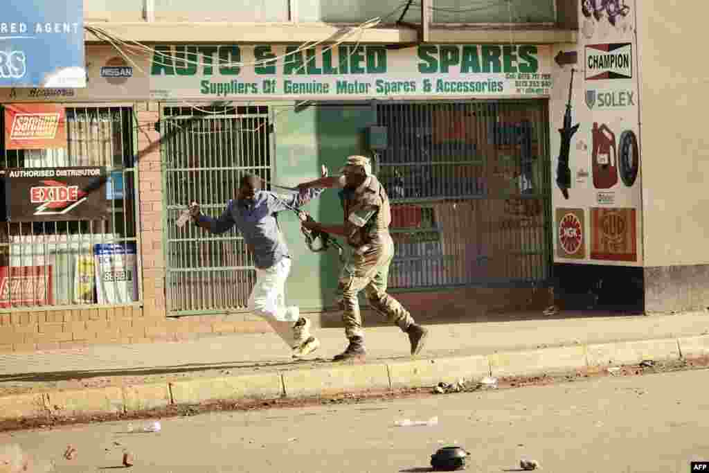 A Zimbabwean soldier strikes a man along a street in Harare after protests erupted over alleged fraud in the country's election.
