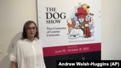 """Anne Drozd, museum coordinator at Ohio State University's Billy Ireland Cartoon Library Museum, stands at the entrance to the library's new exhibit, """"The Dog Show,"""" on Thursday, June 24, 2021, in Columbus, Ohio(AP Photo/Andrew Welsh-Huggins)"""