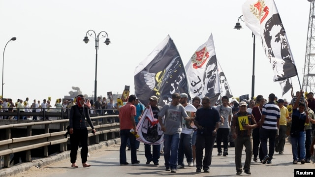 "Members of the Muslim Brotherhood and supporters of ousted Egyptian president Mohamed Morsi shout slogans during a protest named ""People Protect the Revolution"" as they march towards the presidential palace in Cairo, Sept. 6, 2013."