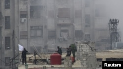 敘利亞反政府戰鬥人員2 月6日在與阿薩德政府軍激戰後在一處建築的天台揮動穆斯林旗幟。
