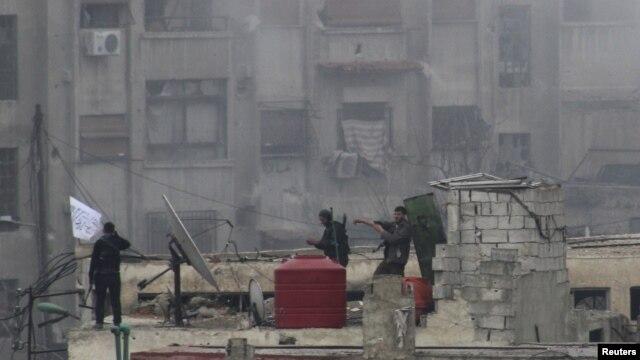 Tentara Pembebasan Suriah mengibarkan bendera Islam di sebuah atap pasca pertempuran hebat melawan pasukan pendukung Presiden Bashar al-Asaad di wilayah Jobar, Damascus, Suriah (6/2).