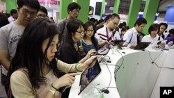 參觀者在展銷會上試用平板電腦