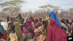 Mothers sit with their children in a compound for internally displaced persons in the Somali border town of Dhobley, August 11, 2011.