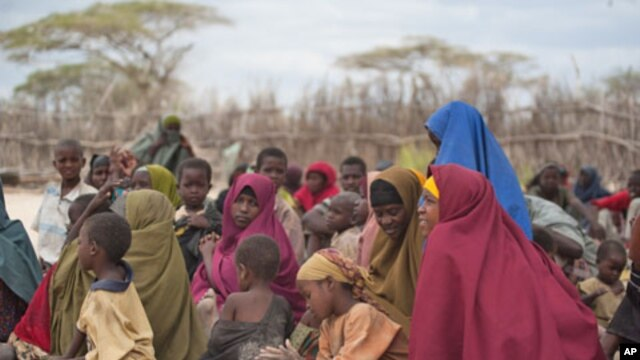 Mothers sit with their children in a compound for internally displaced persons (IDPs) in the Somali border town of Dhobley on August 11, 2011