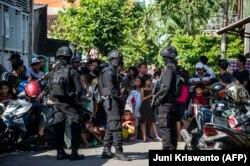 Densus 88 mengepung sebuah jalan ketika mereka menggeledah sebuah rumah di Surabaya, Jawa Timur, pada 19 Juni 2017. (Foto: AFP/Juni Kriswanto)