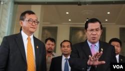 PM Kamboja Hun Sen (kanan) bersama Sam Rainsy, pemimpin partai CNRP (kiri), seusai pemilihan anggota Komisi Pemilu Baru di Phnom Penh, Kambojia, 9 April 2015.