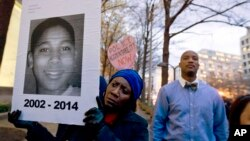FILE - Tomiko Shine holds up a picture of Tamir Rice, the 12-year-old boy fatally shot on Nov. 22 , 2014 by a police officer, in Cleveland, Ohio, Dec. 1, 2014.