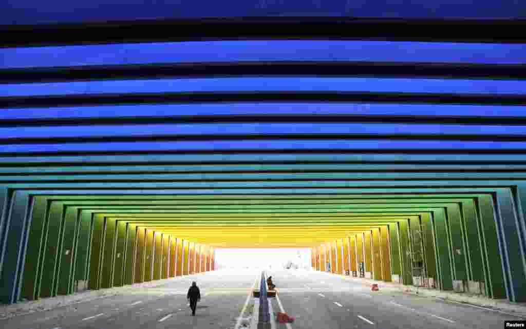 A man walks along a newly-built tunnel, consisting of rainbow colors, in Zhengzhou, Henan province, China.