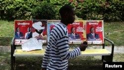 Un homme passe devant les posters des candidats présidentiels de l'élection de 2013, à Nairobi, le 8 mars 2013.