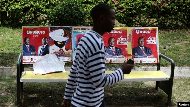 A man passes by posters of presidential candidates Uhuru Kenyatta and Prime Minister Raila Odinga in Nairobi, March 8, 2013.