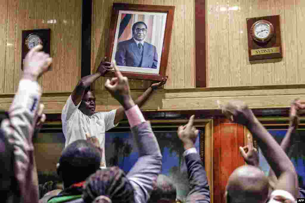 People remove a portrait of former Zimbabwean President Robert Mugabe from the wall at the International Conference center, after his resignation in Harare. Robert Mugabe resigned swept from power as his 37-year reign of brutality and autocratic control crumbled within days of a military takeover.