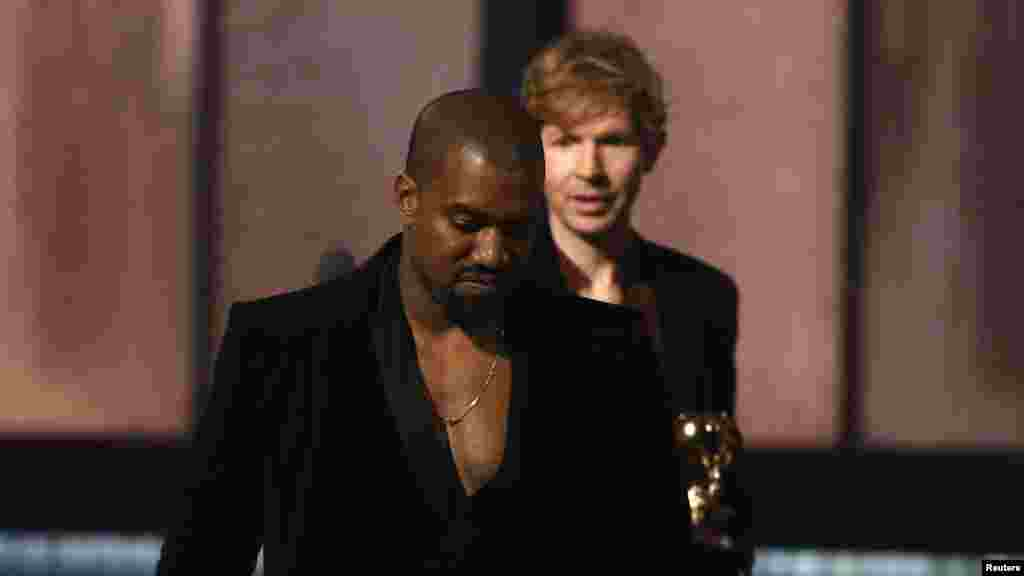 "Beck, background, watches Kanye West, who pretended to take the stage after Beck won album of the year for ""Morning Phase,"" at the 57th annual Grammy Awards in Los Angeles, California, Feb. 8, 2015."