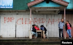 Residents play chess in front of a closed establishment with a sign declaring the area cleared by government troops inside Marawi city, southern Philippines, Oct. 18, 2017.