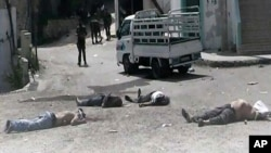 This citizen journalist image provided by The Syrian Revolution against Bashar Assad, which has been authenticated based on its contents and other AP reporting, shows Syrian army soldiers standing in front of dead bodies at Bayda village.