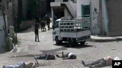 叙利亚西北部的贝达村遭屠杀后的景象,政府军士兵站在一旁