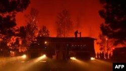 Un pompier sur le toit d'une maison en flammes dans les montagnes de Santa Cruz, en Californie, 27 septembre 2017.