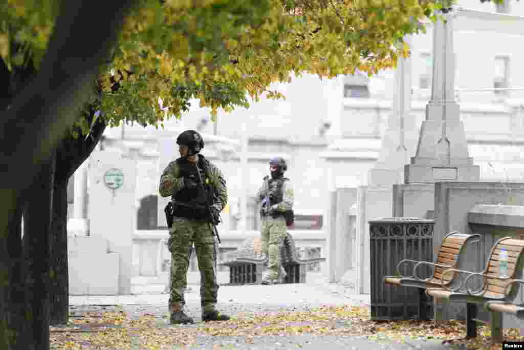Police officers stand guard near the National War Memorial in downtown Ottawa, Oct. 23, 2014.