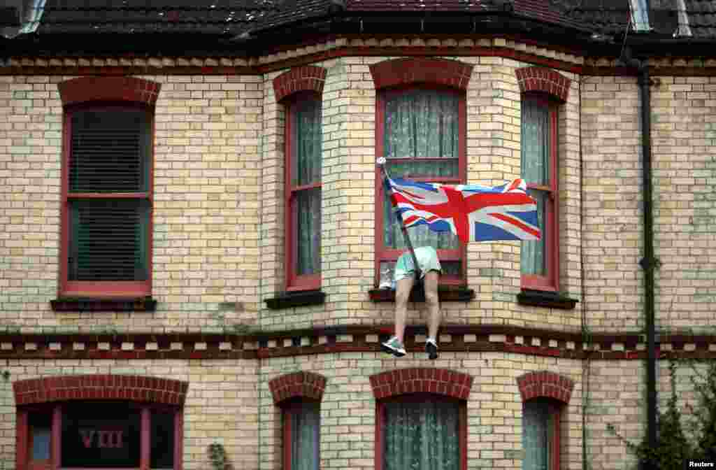 The legs of a mannequin hang out of the window of a house on a residential street in Brighton, Britain, Sept. 18, 2018.