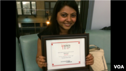 Jinal Shah of the South Asian Times proudly poses with her Ippies Award in New York, June 6, 2014. (A. Phillips/VOA)
